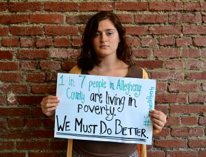 Just Harvest Bonner Leader holding sign: 1 in 7 people in Allegheny County are living in poverty. We Must Do Better.
