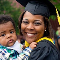 woman graduate holding her child