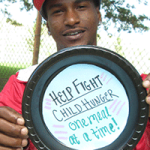 """John from Homewood holds paper plate saying """"Help fight child hunger one meal at a time!"""""""