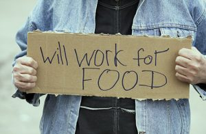 "Man holding sign that says ""Will work for food"""