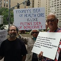 "Toomey protestor carrying sign ""Toomey's idea of healthcare is like Putin's idea of democracy"" via @lisajwardle 