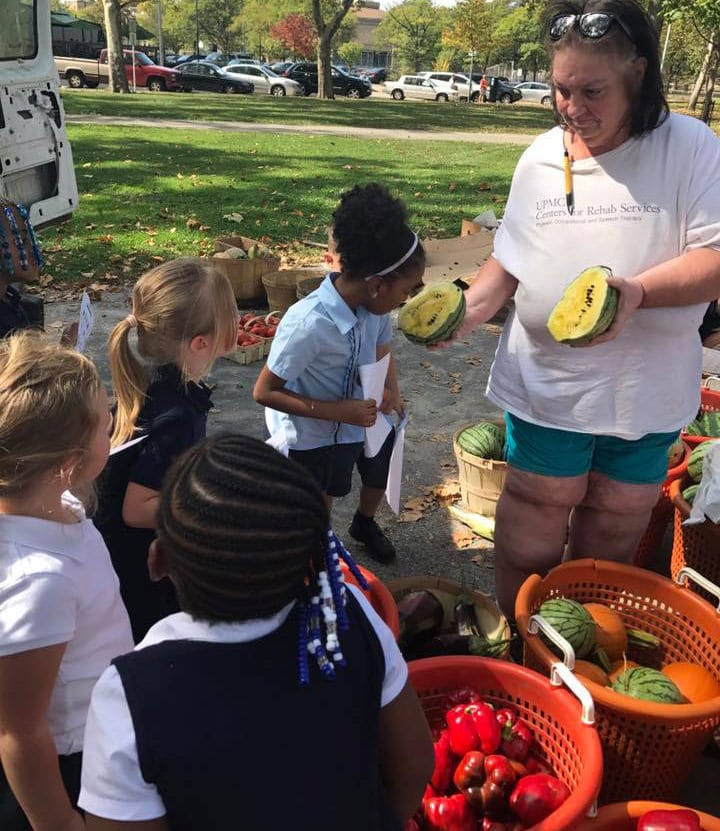 Allegheny Traditional Academy girls investigate melon at the North Side farmers market, Oct. 2017