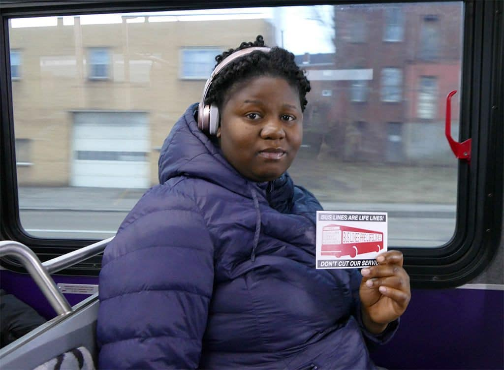 "61ABC bus rider holding ""bus lines are lifelines"" card"