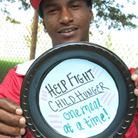 "John from Homewood holds paper plate saying ""Help fight child hunger one meal at a time!"""