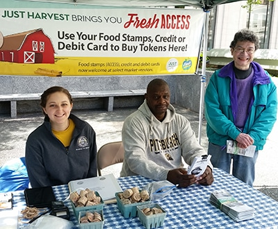 Just Harvest volunteers at a Fresh Access farmers market booth