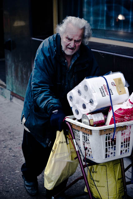 older man pushing groceries (via Flickr/Christos Tsirbas)