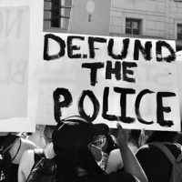 Protester with Defund the Police sign via flickr/Taymaz Valley